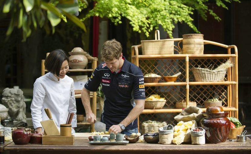 """El tricampeón alemán de Fórmula Uno, Sebastian Vettel, toma una """"clase"""" de cocina en China. (Agencias)"""