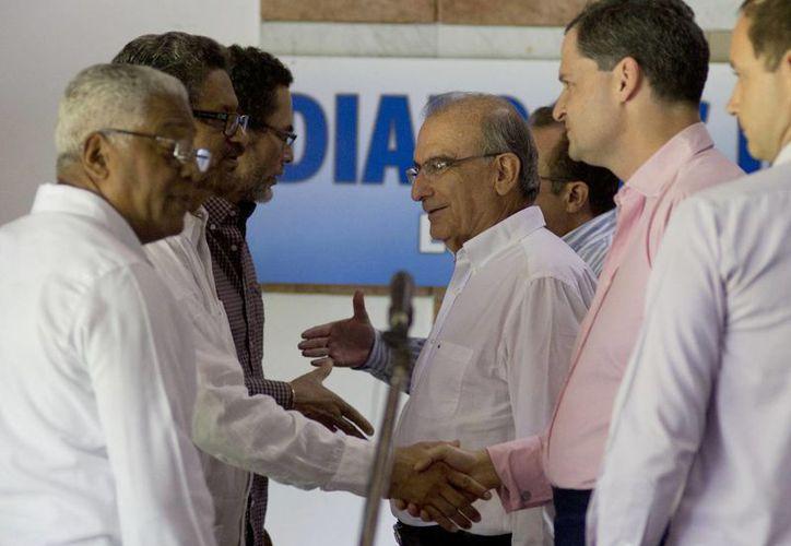 Humberto de la Calle, titular de la delegación del gobierno colombiano (c), dialoga con el jefe rebelde Iván Márquez tras la reanudación de las conversaciones de paz entre el gobierno del presidente Juan Manuel Santos y las FARC, en La Habana, Cuba. (Agencias)