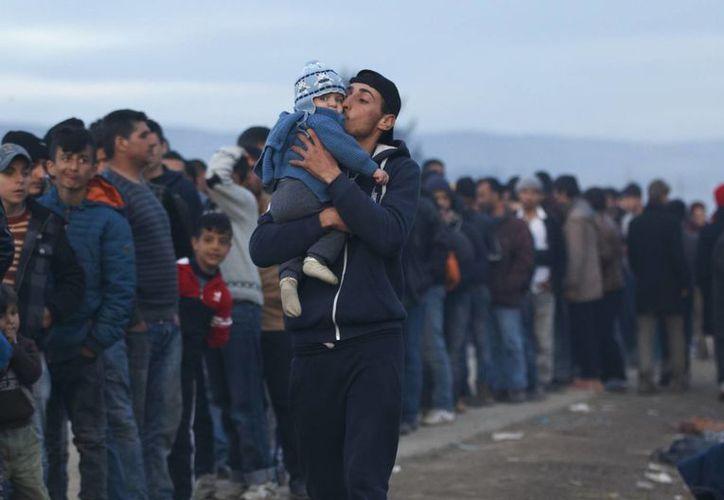 Un migrante besa a un niño cerca de una larga fila de gente esperando para las raciones de sopa caliente en la estación de frontera griega norte de Idomeni. Turquía aseguró que no recibiría a los inmigrantes ya instalados en Grecia. (Foto AP / Vadim Ghirda)