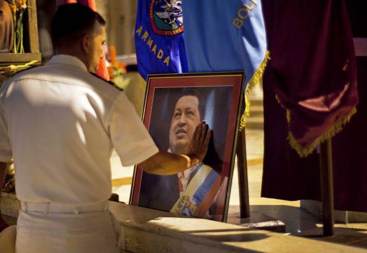 Un miembro de la armada de Venezuela toca una imagen del presidente de Venezuela. (Agencias)