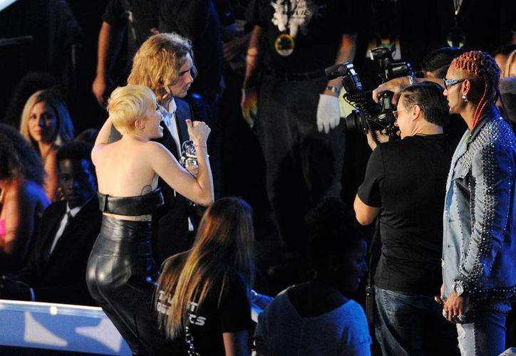 Tras recibir el MTV Music Award, la cantante Miley Cyrus posa para la foto, acompañada de Jesse Helt, un indigente que acudió para 'hacer conciencia' sobre  el problema de la gente sin hogar. El joven, buscado por la policía, se entregó este viernes. (Archivo/AP)