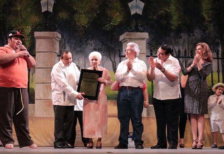 Aicela Hernández Alcocer <i>Chichí</i>, recibe una placa de reconocimiento de manos del titular de la Sedeculta, Roger Metri Duarte. (SIPSE)
