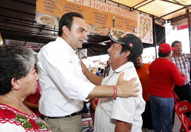 Nerio Torres Arcila platica con un locatario durante su recorrido por los mercados Lucas de Gálvez y San Benito. (SIPSE)