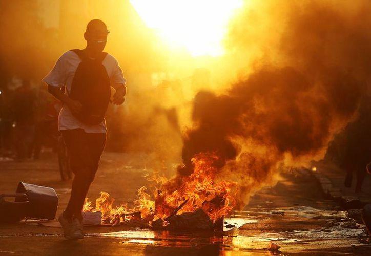 Con bombas de gas lacrimógeno, la policía evacuó a los manifestantes en Río de Janeiro. (EFE)