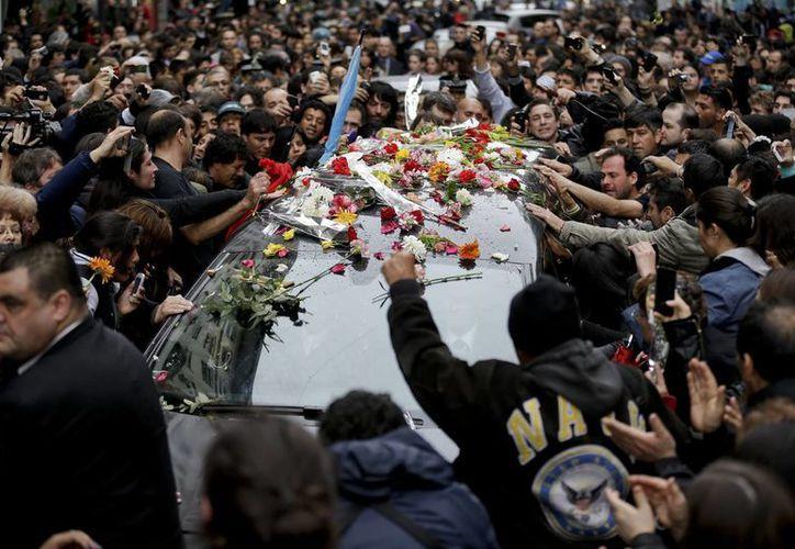 Dolientes tocan el coche fúnebre que transporta los restos del astro del rock argentino Gustavo Cerati a un cementerio en Buenos Aires. (Agencias)