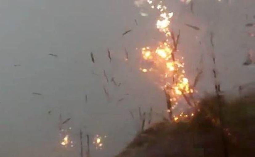 Un rayo impactó en un poste y lo destruyó en instantes, mientras los pedazos caían sobre una avenida transitada en Chicago. (Captura de pantalla)