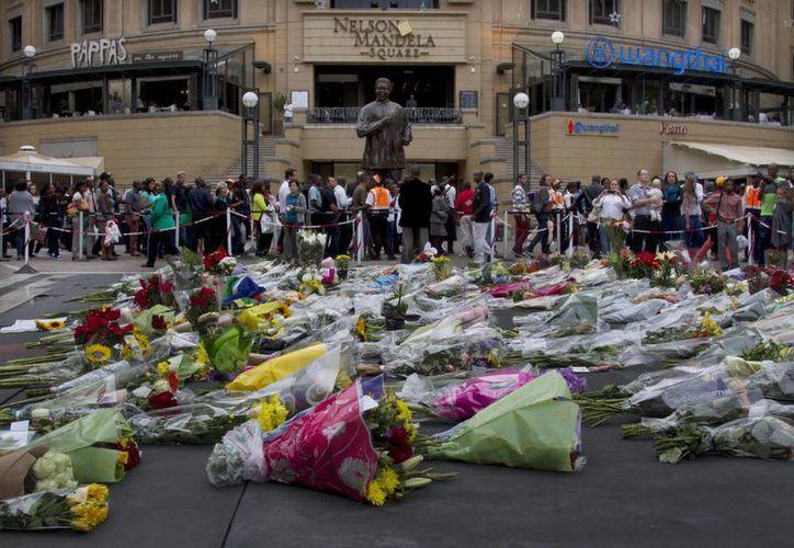 México fue uno de los primeros países en reconocer la República de Sudáfrica que impulsó Mandela. En la imagen, cientos de arreglos florales ante  una estatua del extinto líder en Johannesburgo. (Agencias)