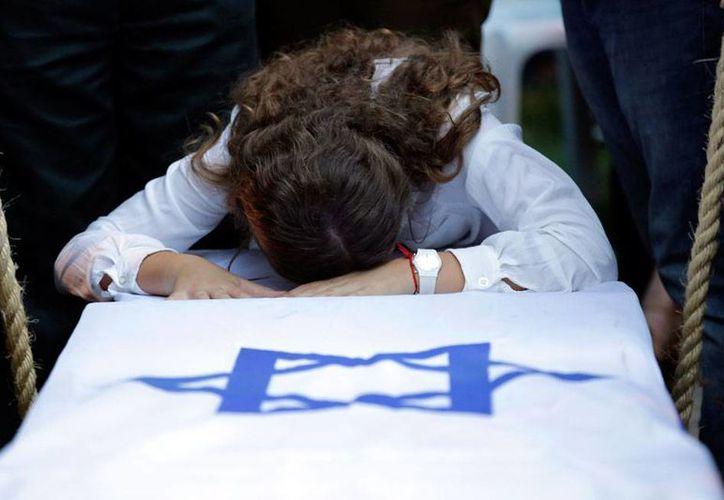 Miles de 'voluntarios' de otros países se enfilan en el Ejército hebreo para combatir a los palestinos. En la imagen, un deudo del soldado Jordan Ben-Simon -con ciudadanía francesa- llora la muerte del militar. (AP)