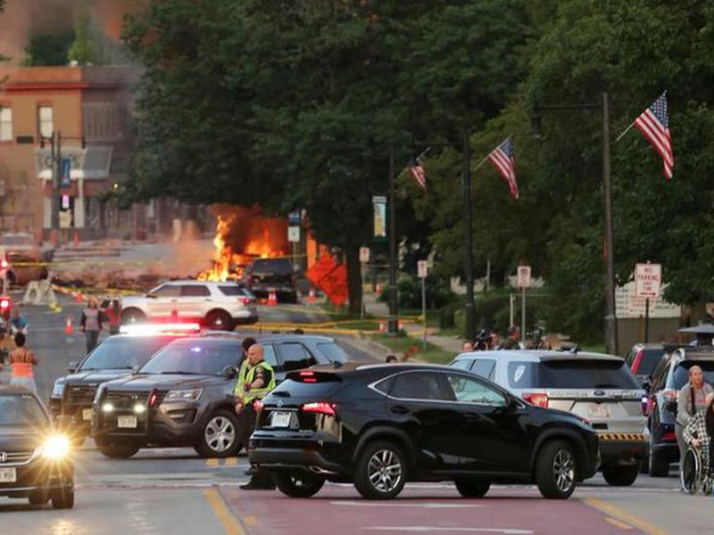 Police officers shut down a street as firefighters work the scene of an  explosion in downtown Sun Prairie, Wis.