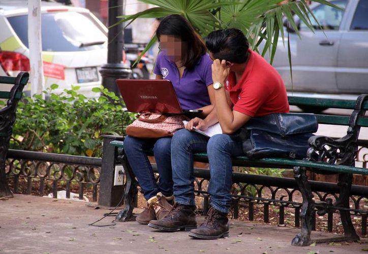 Para los jóvenes emprendedores internet es una herramienta clave. Imagen de un par de estudiantes en una banca de la Plaza Grande de Mérida. (Milenio Novedades)