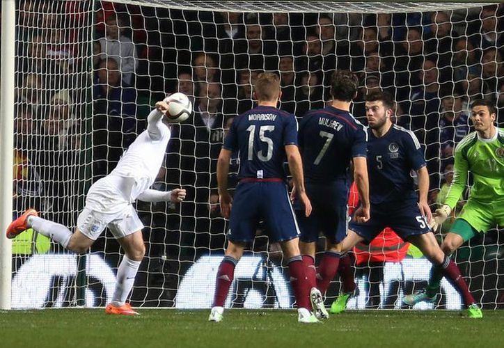 Wayne Rooney (i) anota uno de sus goles en el partido amistoso contra Escocia en Glasgow. (Foto: AP)