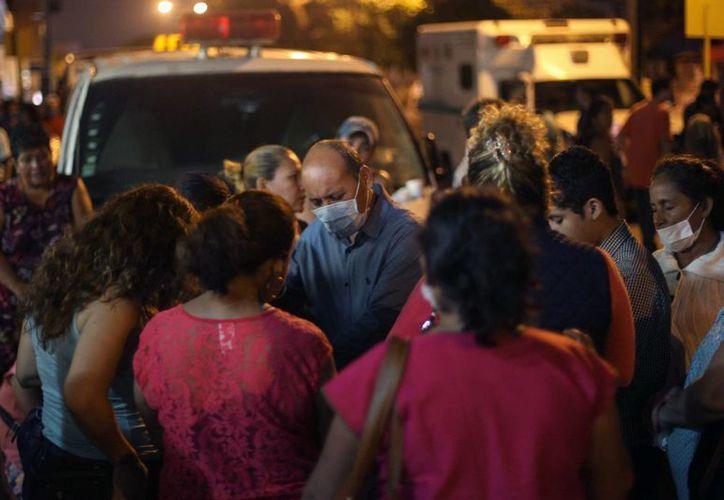 Familiares de trabajadores desaparecidos por la explosión rezan mientras esperan noticias sobre sus seres queridos. (Agencias)