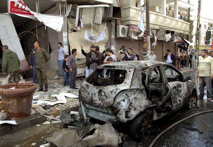 Varios ciudadanos sirios y policías examinan el lugar de un atentado en Homs, Siria. (EFE)