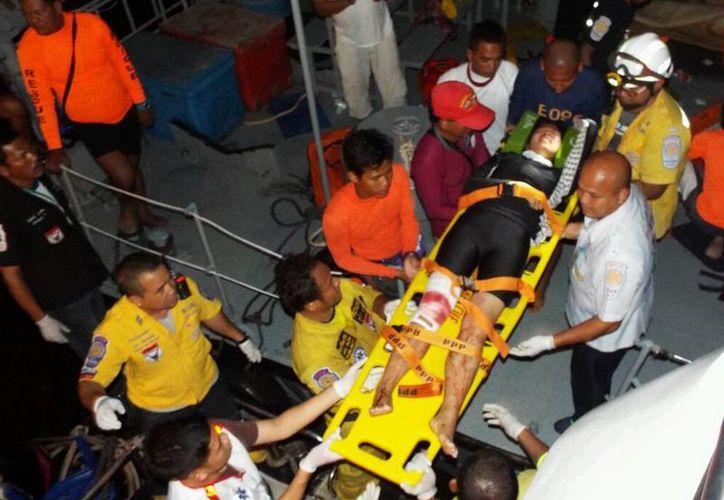 Rescatistas cargan en una camilla a una turista herida hacia un hospital después de un choque entre dos barcos cerca del muelle de Phuket, Tailandia, el domingo 19 de octubre de 2014. (Foto AP)
