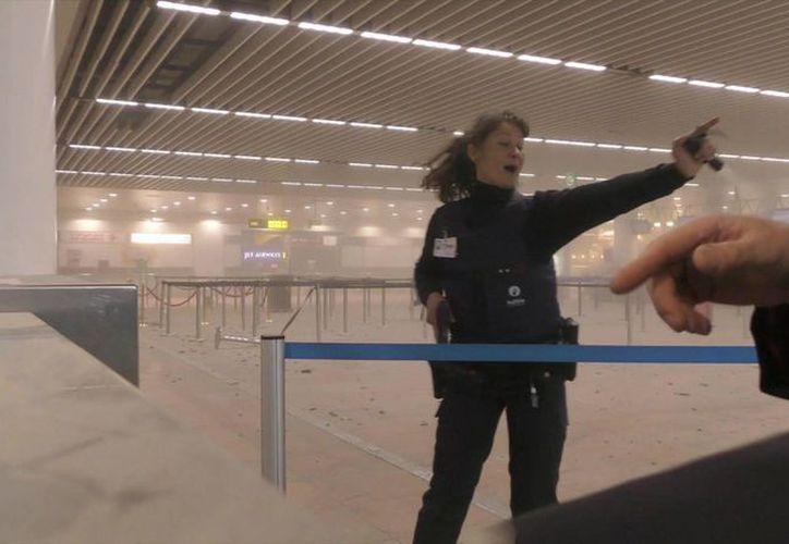 Un policía dirige a los pasajeros en el aeropuerto Zaventem de Bruselas, tras las explosiones registradas la mañana del martes 22 de marzo de 2016. (Agencias)