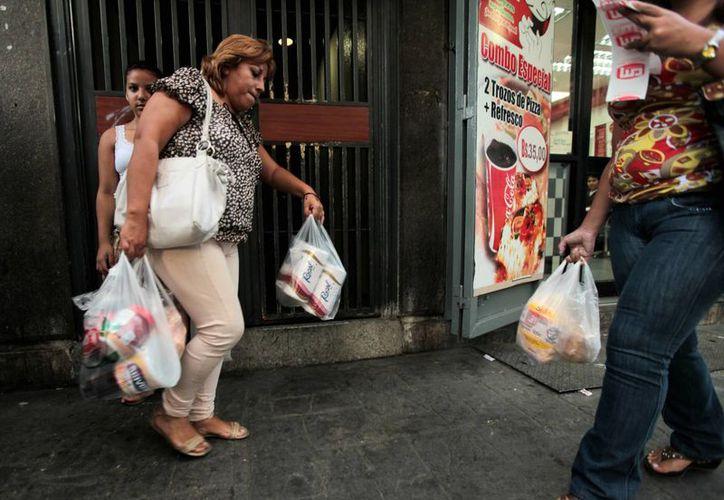 Una cliente sale de un supermercado privado con sus compras en Caracas, Venezuela, país que lucha por controlar una inflación galopante, escasez de productos y reclamos de aumentos salariales. (Agencias)