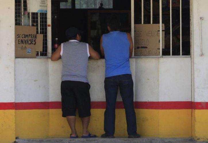 Queda prohibido el suministro y distribución de bebidas alcohólicas por la Ley Seca, desde el sábado hasta el lunes. La imagen, de dos hombres en las puertas de una cervecería, está utilizada como contexto. (Archivo/SIPSE)