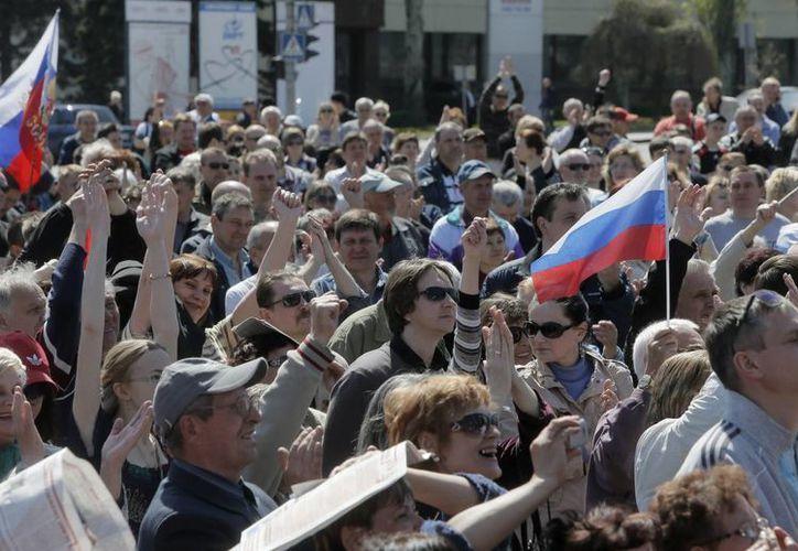 Manifestación del domingo, donde los participantes ondean banderas rusas en la Plaza Lenin en Donetsk, Ucrania. (Agencias)