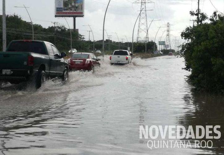 La inundaciones tras las tormentas han causado con autos queden varados. (Redacción)