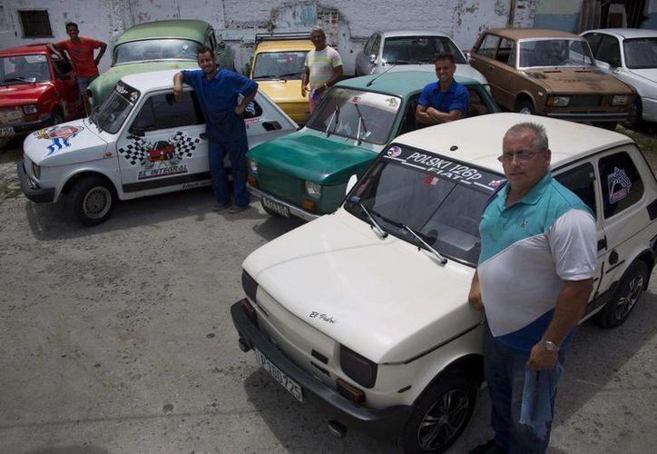 Los propietarios de Fiat Polski 126p, Raúl Seoane (izq), Ramsés Fernández (segundo por la izquierda), Evilio Aguilar (c), Rigoberto Mesa (segundo por la derecha) y Pedro Fernández, posan orgullosos junto a sus autos en La Habana.