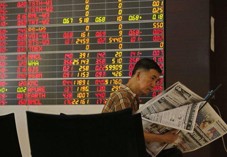 Los mercados asiáticos subieron durante la jornada luego del rebote en Wall Street durante la noche. Imagen de un inversor junto a un panel con información bursátil en Tailandia. (EFE)