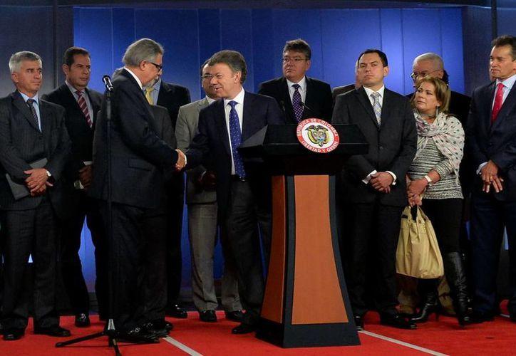 El mandatario colombiano Juan Manuel Santos (c) estrechando la mano del presidente de la Sociedad de Agricultores de Colombia (SAC), Rafael Mejía (i) en Bogotá, Colombia. (EFE)