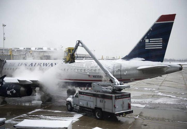 """Trabajadores limpian de nieve un avión en el aeropuerto """"Ronald Reagan"""" en Arlington, Estados Unidos. (EFE)"""