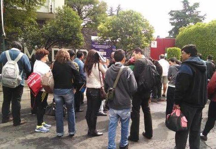 Padres de familia esperan a sus hijos durante la aplicación del examen de la UNAM. (Milenio)