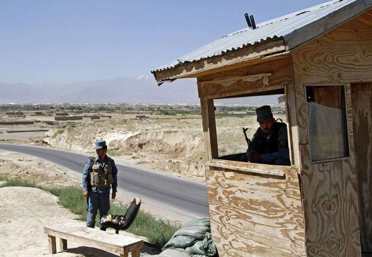 Policías afganos vigilan afuera de la base militar de Bagram, 50 kilómetros al norte de Kabul, Afganistán. (Agencias)