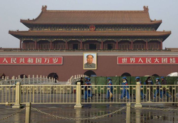 Trabajadores colocan escudos verdes frente a la Plaza Tiananmen después de que un vehículo se estrelló contra una barrera protectora. (Agencias)