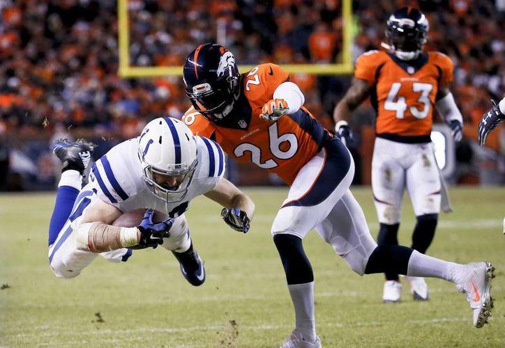 Jack Doyle, de los Colts de Indianápolis, es sacado del terreno por Rahim Moore, safety de los Broncos de Denver. (AP Foto/Jack Dempsey)