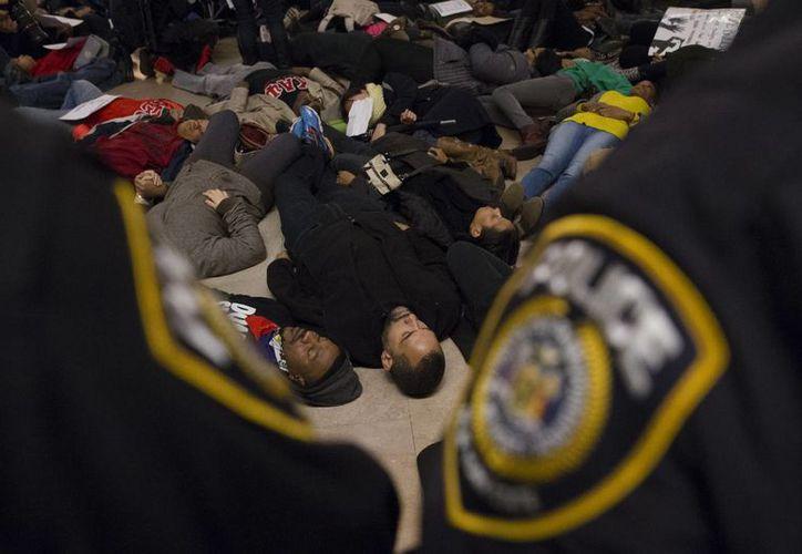 Los manifestantes realizan una protesta en la estación Grand Central, mientras la policía hacen guardia. (Agencias)