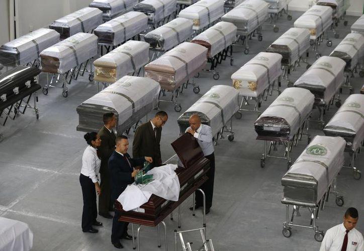 Los empleados funerarios se preparan para cubrir un ataúd con una sábana blanca con el logotipo del equipo de fútbol Chapecoense que contiene los restos de un miembro del equipo en la funeraria de San Vicente en Medellín, Colombia. (AP/Fernando Vergara)