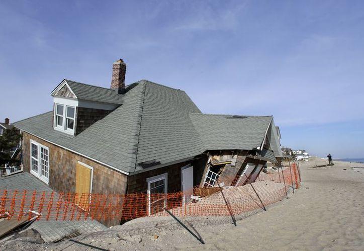 Un hombre toma fotografías de una casa en la playa en Bay Head, Nueva Jersey, que fue dañada hace dos meses por la supertormenta. (Agencias)