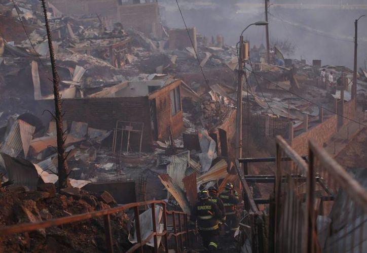 Las autoridades decretaron alerta roja en Valparaíso por un incendio que ha consumido al menos 50 casas. (AP/Luis Hidalgo)