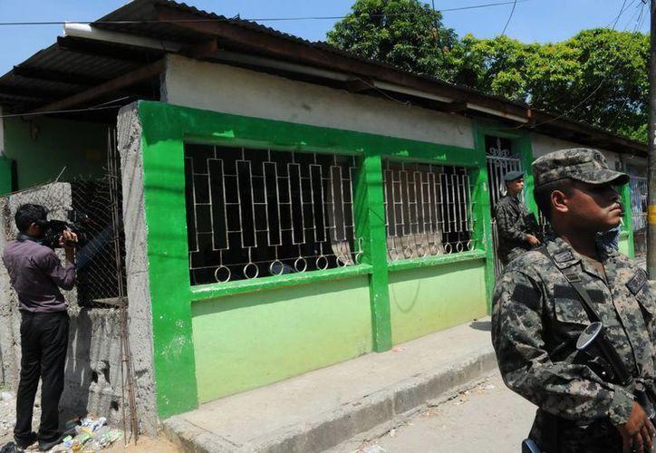 Soldados hondureños vigilan la casa donde fueron encontrados los cuerpos de cinco miembros de una misma familia. (EFE)