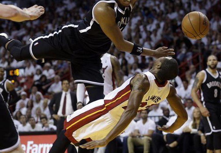 Paul Pierce, de Nets, es fauleado por James Jones (22), de Heat, durante la segunda mitad del quinto partido eliminatorio. (Foto: AP)