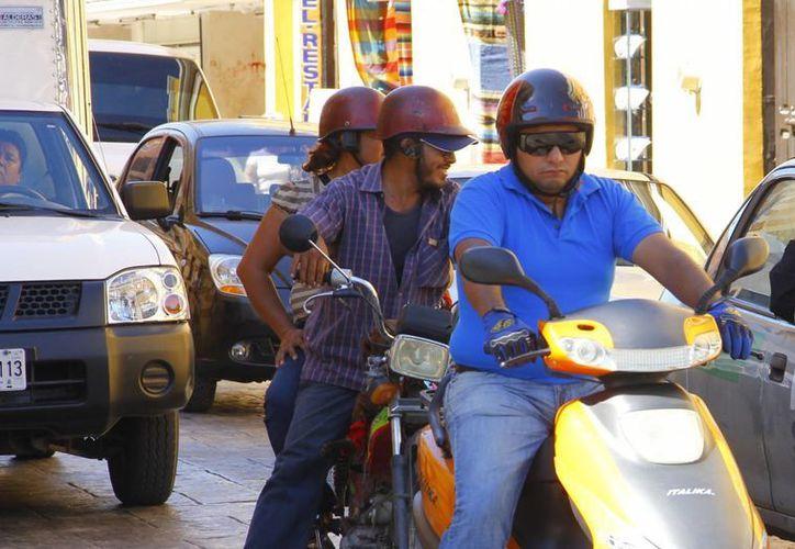 El casco reduce 39 por ciento la probabilidad de muerte de los conductores del vehículo de dos ruedas. Imagen de contexto de motociclistas circulando en el Centro histórico de Mérida. (Milenio Novedades)