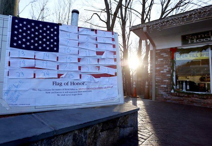 Una bandera de los EU luce cubierta con números que representan las víctimas de la matanza en la escuela primaria Sandy Hook de Newton, Connecticut. (Agencias)