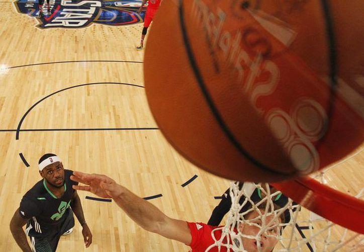 Blake Griffin, de Los Angeles Clippers (32) y de la Conferencia Oeste, encesta ante la mirada atónita de LeBron James, del Miami Heat (6) y de la Conferencia Este, que vino de atrás y venció en el Juego de Estrellas. (Agencias)