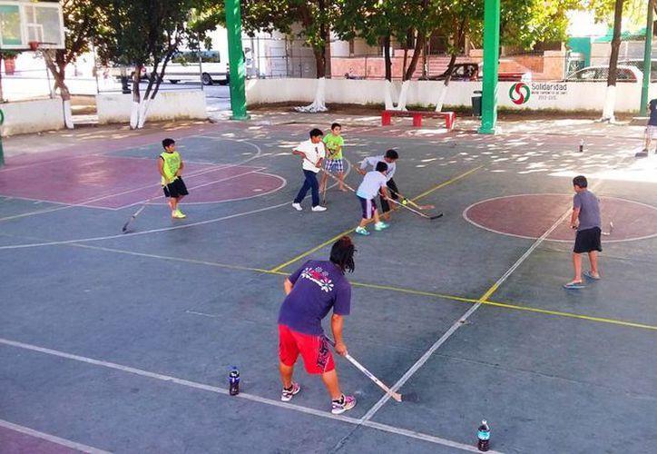 La asociación Keeping Kids in School (KKIS) da clases de hockey en el domo de la colonia Gonzalo Guerrero. (Daniel Pacheco/SIPSE)