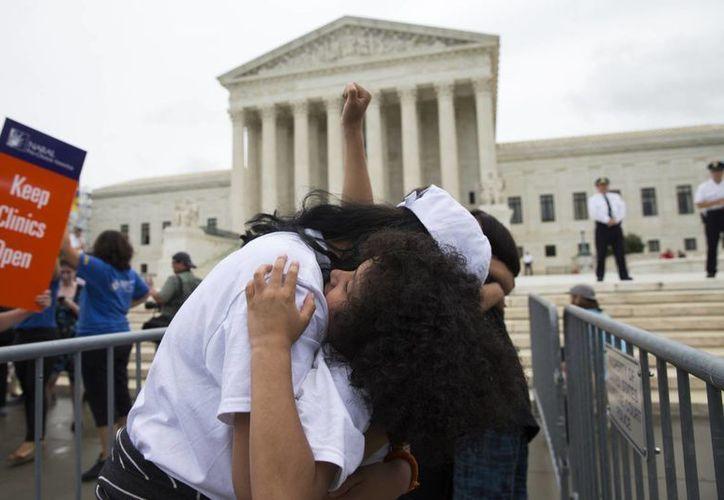 Jackelin Alfaro (der) abraza a su tía Gelin Alfaro, de Veracruz, tras el conocerse el fallo de la Suprema Corte de Justicia sobre el alivio migratorio propuesto por el gobierno de Obama. (Agencias)