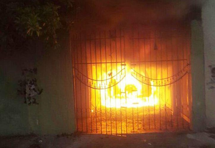 El fuego incineró prácticamente el vehículo estacionado en la cochera de un domicilio, en la colonia El Porvenir. (Aldo Pallota/SIPSE)