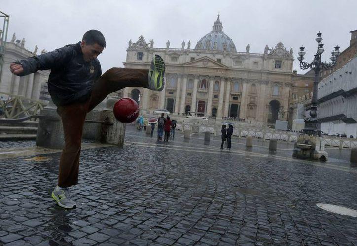 Un muchacho juega en la Plaza de  San Pedro, en Roma, donde una pertinaz lluvia cayó este lunes. (AP)