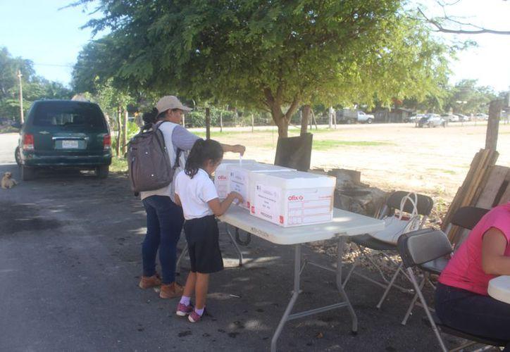 Los votantes presentan su credencial de elector para sufragar. (Sara Cauich/SIPSE)
