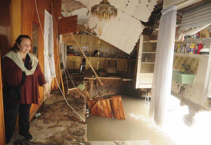 Una mujer en el interior de su casa afectada por el fuerte temporal de lluvias en La Plata, Argentina. (EFE)