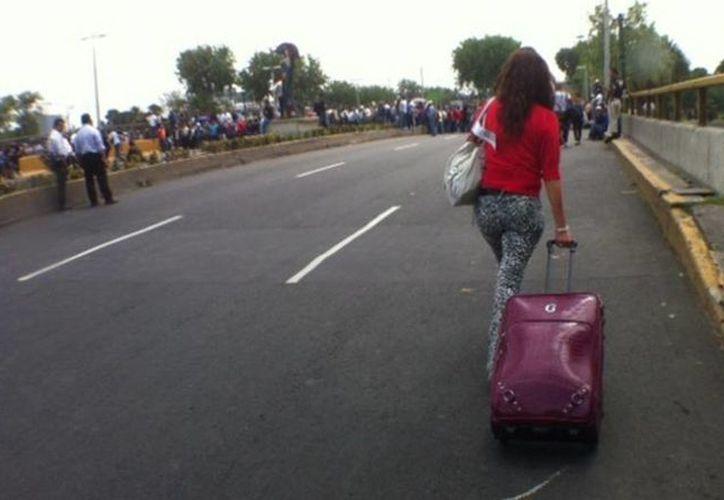Los pasajeros buscan desesperados la forma de llegar puntuales al aeropuerto. (Milenio)