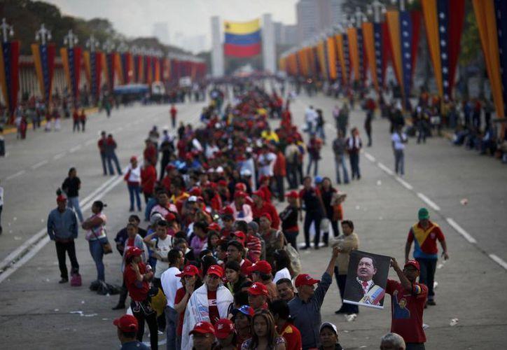 Venezolanos hacen fila a las afueras de la Academia Militar donde reposa el cuerpo de Chávez. (Agencias)