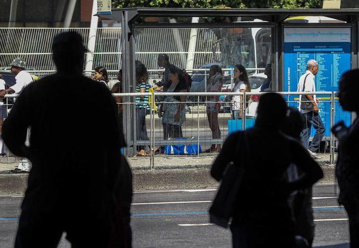 Un grupo de personas espera algún medio de transporte en la ciudad de Río de Janeiro, que amaneció sin gran parte de sus autobuses en las calles debido a una huelga de 24 horas. (EFE)