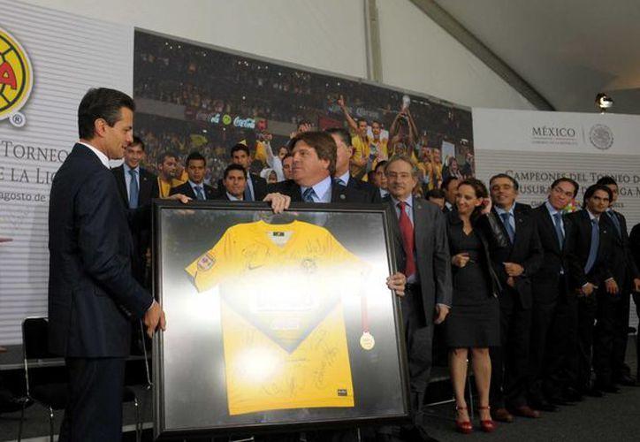 El entrenador americanista Miguel Herrera hace entrega de una playera del club de Coapa al presidente de México. (Notimex)